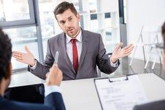 Uomo d'affari che gesturing durante l'intervista di lavoro Immagini Stock