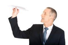 Uomo d'affari che getta un aereo di carta Fotografia Stock Libera da Diritti