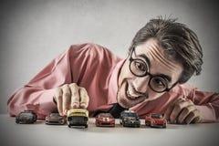 Uomo d'affari che gioca con le piccole automobili Fotografia Stock Libera da Diritti