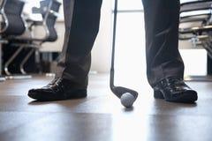 Uomo d'affari che gioca golf nel suo ufficio, fine su sui piedi Immagine Stock