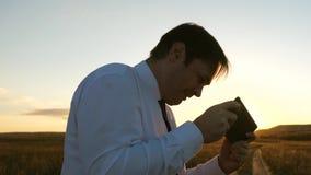 Uomo d'affari che gioca i giochi della compressa nel parco nei raggi caldi del tramonto uomo che gioca sullo smartphone felice stock footage