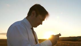 Uomo d'affari che gioca i giochi della compressa nel parco nei raggi caldi del tramonto uomo che gioca sullo smartphone felice video d archivio