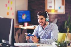 Uomo d'affari che gioca i videogiochi nel suo ufficio Immagini Stock