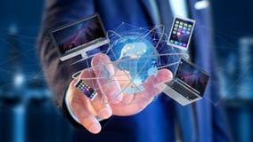 Uomo d'affari che giudica un computer ed i dispositivi visualizzati su un futuri Immagine Stock Libera da Diritti