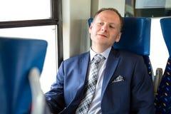 Uomo d'affari che gode del suo viaggio in treno immagine stock