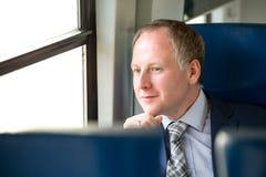 Uomo d'affari che gode del suo viaggio in treno Immagini Stock