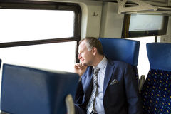 Uomo d'affari che gode del suo viaggio in treno Immagini Stock Libere da Diritti