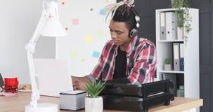 Uomo d'affari che gode della musica mentre attaccando nota adesiva sul computer portatile video d archivio