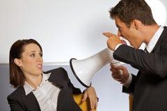 Uomo d'affari che grida alla donna di affari tramite il megafono e che gesturing il segno della pistola Fotografia Stock Libera da Diritti