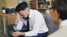 Uomo d'affari che grida sofferenza dalla depressione durante l'appuntamento con il terapista archivi video