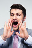 Uomo d'affari che grida sopra il fondo grigio Immagini Stock