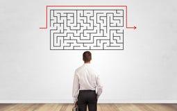 Uomo d'affari che guarda ad un labirinto su una parete fotografia stock libera da diritti