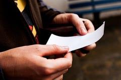Uomo d'affari che guarda ad una carta vuota Il Libro Bianco vuoto dentro equipaggia le mani Foglio di carta della tenuta maschio  Immagine Stock