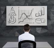 Uomo d'affari che guarda al grafico Immagine Stock
