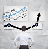 Uomo d'affari che guarda al grafico Fotografie Stock