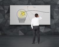 Uomo d'affari che guarda alla lampada sul manifesto Immagini Stock Libere da Diritti