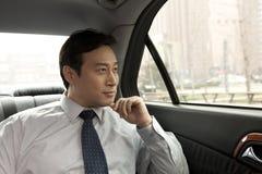 Uomo d'affari che guarda fuori la finestra di automobile Immagine Stock