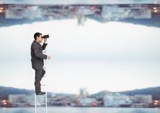 Uomo d'affari che guarda lontano con il binocolo vicino ad una città fotografie stock