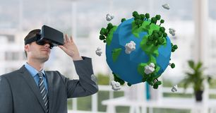 Uomo d'affari che guarda terra 3D con i vetri virtuali Immagini Stock