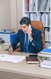 Uomo d'affari che ha discussione dal telefono in ufficio Fotografie Stock
