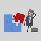 Uomo d'affari che ha problema con un puzzle Fotografia Stock Libera da Diritti