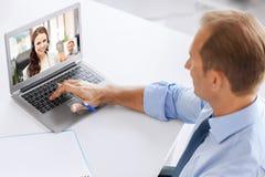 Uomo d'affari che ha video chiamata sul computer portatile all'ufficio immagini stock libere da diritti