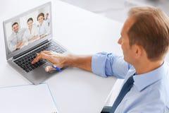 Uomo d'affari che ha videoconferenza all'ufficio fotografia stock libera da diritti