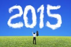 Uomo d'affari che incoraggia per una forma di 2015 nuvole con l'erba del cielo blu Immagini Stock