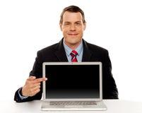 Uomo d'affari che indica allo schermo in bianco del computer portatile Fotografia Stock