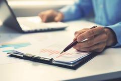 Uomo d'affari che indica con la penna sul grafico annuale della relazione di attività fotografia stock