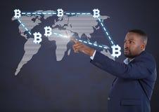 Uomo d'affari che indica con le icone grafiche del bitcoin sulla mappa di mondo Fotografia Stock