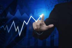 Uomo d'affari che indica il grafico ed il grafico di affari della freccia sopra la mappa Fotografia Stock