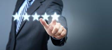 Uomo d'affari che indica il simbolo di valutazione di servizio di cinque stelle immagini stock libere da diritti