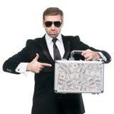 Uomo d'affari che indica il suo dito verso la valigia del metallo Fotografia Stock