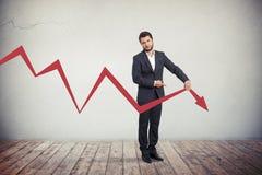 Uomo d'affari che indica la freccia rossa del grafico giù Fotografie Stock