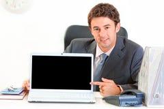 Uomo d'affari che indica sul computer portatile con lo schermo in bianco Fotografia Stock