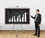Uomo d'affari che indica sul grafico Fotografia Stock