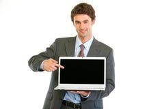 Uomo d'affari che indica sullo schermo in bianco dei computer portatili Fotografia Stock