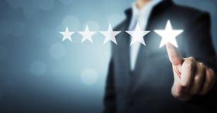 Uomo d'affari che indica un simbolo di cinque stelle la valutazione di aumento dei comp. Fotografie Stock