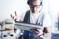 Uomo d'affari che indossa audio cuffia avricolare e che fa video conversazione tramite compressa digitale Uomo elegante che lavor fotografia stock