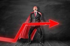 Uomo d'affari che indossano la maschera rossa del superman e mantello che tiene la freccia rossa del diagramma su fondo nero royalty illustrazione gratis