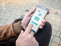 Uomo d'affari che invia messaggio di posta elettronica tramite smartphone moderno Fotografie Stock