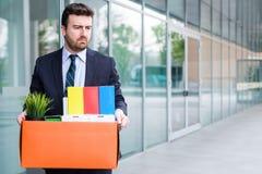 Uomo d'affari che lascia il suo ufficio dopo il fallimento di banca Immagini Stock