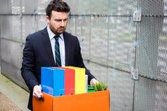 Uomo d'affari che lascia il suo ufficio dopo il fallimento di banca Immagine Stock