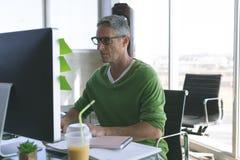 Uomo d'affari che lavora al computer allo scrittorio in ufficio immagine stock libera da diritti