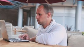 Uomo d'affari che lavora al computer portatile in caffè video d archivio