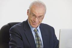 Uomo d'affari che lavora al computer portatile che esamina macchina fotografica. Fotografie Stock