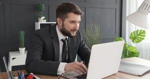 Uomo d'affari che lavora al computer portatile e che celebra stock footage