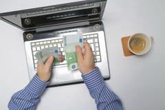 Uomo d'affari che lavora al computer portatile e che conta soldi Fotografie Stock