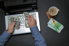 Uomo d'affari che lavora al computer portatile e che conta soldi Fotografia Stock